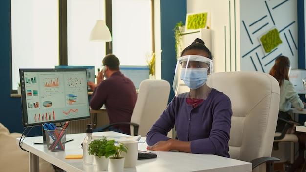 Schwarzer mitarbeiter mit visier und schutzmaske, der die kamera im neuen normalen büro ernst ansieht. multiethnisches geschäftsteam, das in finanzunternehmen arbeitet und die soziale distanz während der globalen pandemie respektiert.