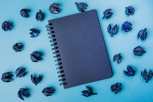 Schwarzer notizblock auf einem blauen hintergrund umgeben durch schwarze trockene anlagen.