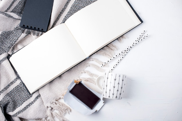 Schwarzer notizblock, cup und plaid auf weißem hintergrund