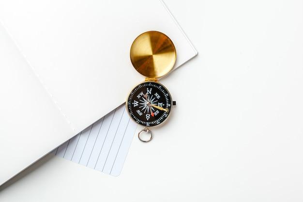 Schwarzer notizblock für seeanmerkungen und goldenen kompass auf einer weißen tabelle