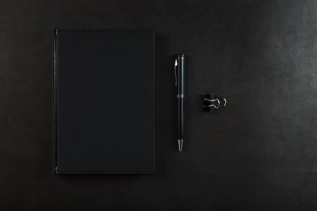 Schwarzer notizblock mit einem schwarzen stift auf einem schwarzen hintergrund. draufsicht, minimalistisches konzept. freiraum.