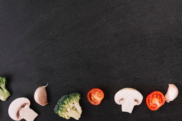 Schwarzer oberflächenhintergrund mit pilz; brokkoli; knoblauchzehe und kirschtomaten