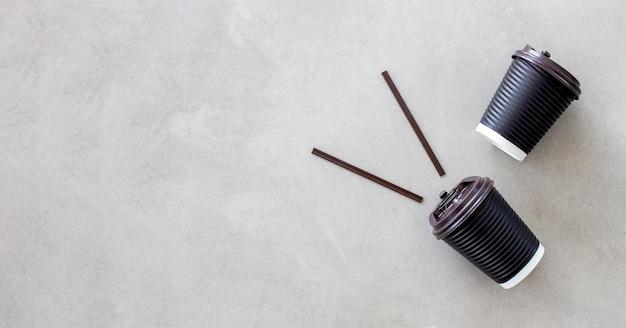 Schwarzer papierbecher kaffee auf zementbodenhintergrund