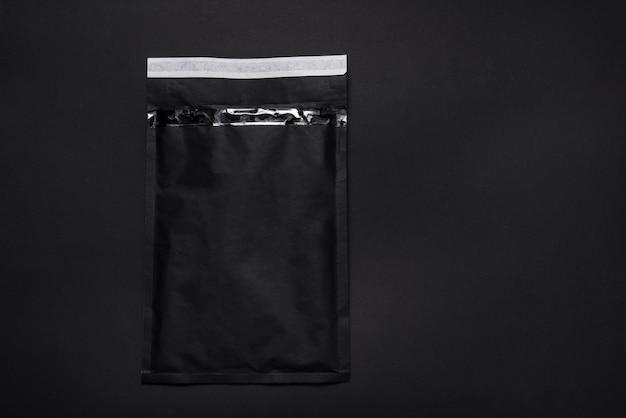 Schwarzer papierblasenumschlag auf dunklem hintergrund