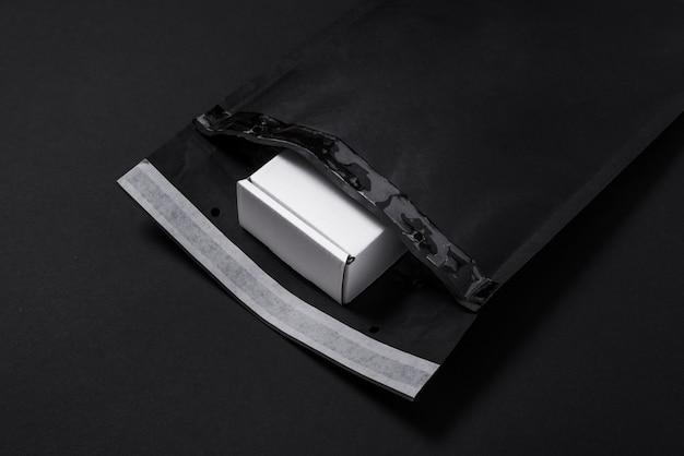 Schwarzer papierblasenumschlag und weißer karton auf dunklem hintergrund