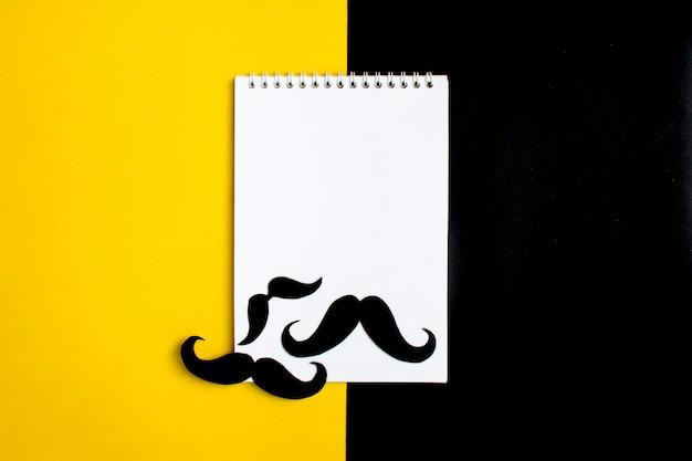 Schwarzer papierschnurrbart, notizblock, bleistift, gelber hintergrund monatliche spendenkontrolle der prosta
