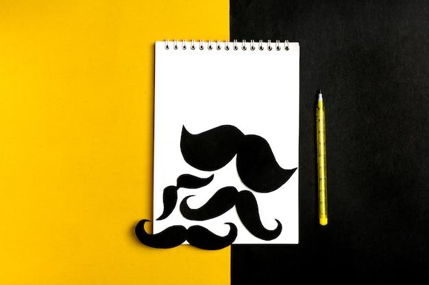 Schwarzer papierschnurrbart, notizblock, stift, gelber hintergrund