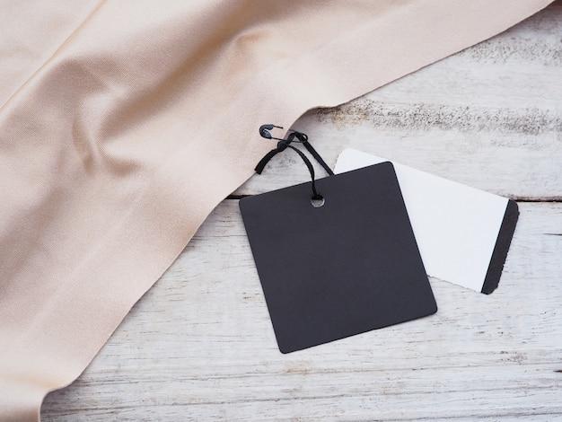 Schwarzer papierverkaufsanhänger, der auf seidentuch über weißem weinleseholzhintergrund hängt.