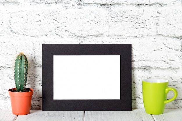 Schwarzer pappfotorahmen auf weißer tabelle gegen backsteinmauer. modell gegen backsteinmauer. attrappe, lehrmodell, simulation