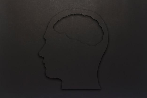Schwarzer pappkopf mit einem gehirn auf einem schwarzen hintergrund. speicherplatz kopieren. flache lage, draufsicht.