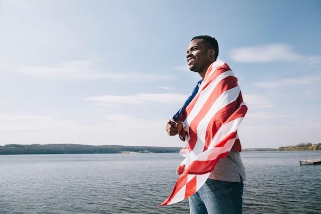 Schwarzer patriotischer mann eingewickelt in der amerikanischen flagge