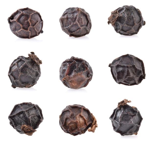 Schwarzer pfeffer getrennt auf weiß. pfefferkorn-sammlung. makro. volle schärfentiefe.