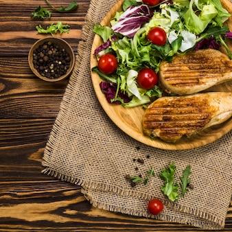 Schwarzer pfeffer in der nähe von salat und brathähnchen
