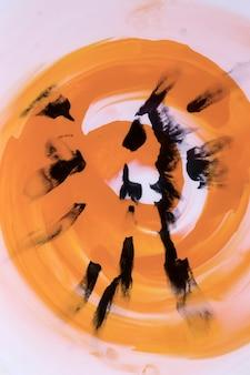 Schwarzer pinselstrich auf strudelorangen-aquarell
