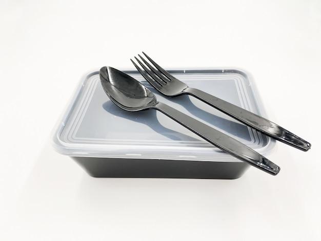Schwarzer plastiknahrungsmittelbehälter mit löffel und gabel auf weiß