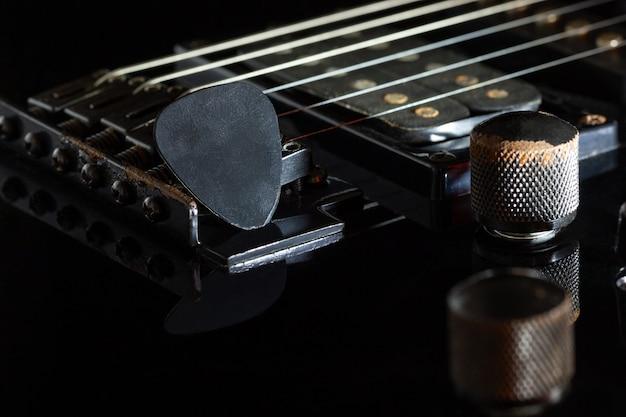 Schwarzer plektrum auf schwarzer e-gitarre in der dunkelheit. konzept des rockmusikstils.