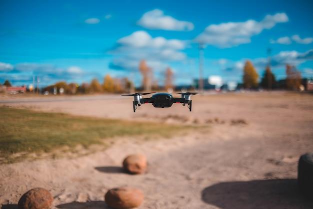 Schwarzer quadcopter, der draußen schwebt
