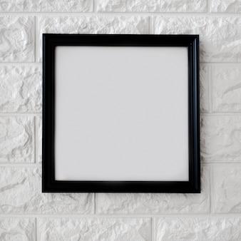 Schwarzer rahmen auf weißer backsteinmauer