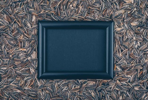 Schwarzer rahmen der draufsicht auf schwarzem sonnenblumenkernhintergrund. horizontaler freier speicherplatz für ihren text