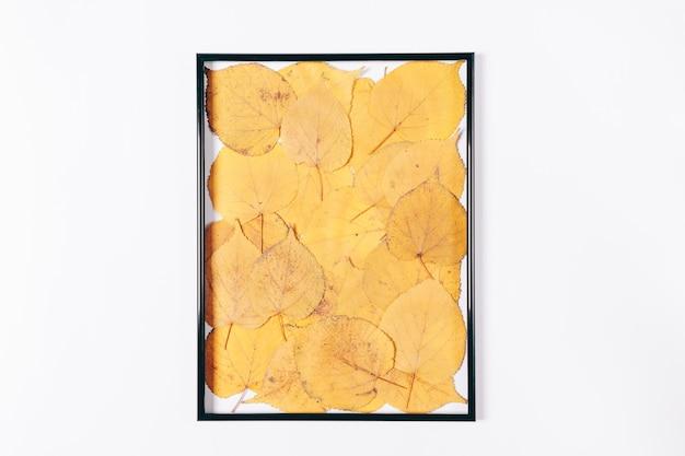 Schwarzer rahmen gefüllt mit trockenem gelbem herbstlaub