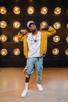 Schwarzer rapper in mütze, leistung auf der bühne mit scheinwerfern