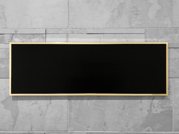 Schwarzer rechteckspott oben mit goldenem rahmen auf grauem marmorbacksteinmauerhintergrund.