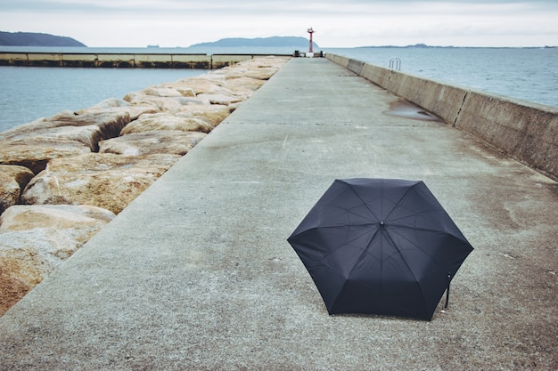 Schwarzer regenschirm auf der fußwegweise. nahe dem meer.