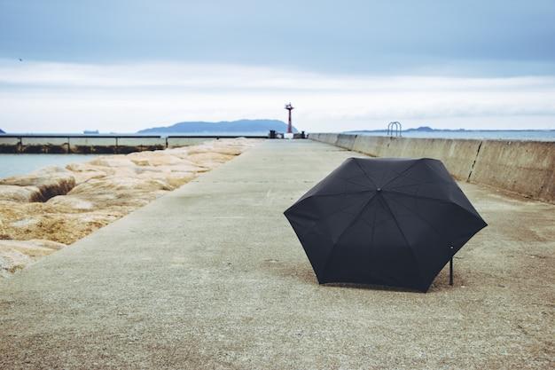 Schwarzer regenschirm auf der fußwegweise