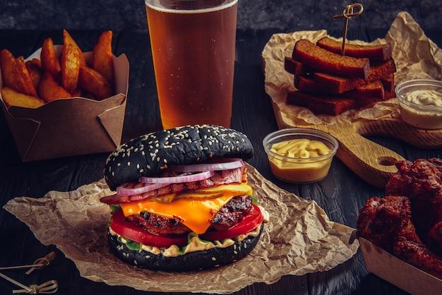 Schwarzer rindfleischburger mit geschmolzenem käse und speck, gebratenen hühnerflügeln, pommes frites