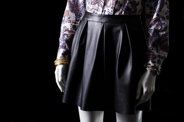 Schwarzer rock, uhr und armband. rock mit falten auf schaufensterpuppe. hochwertiger lederrock für mädchen. brandneue designerklamotten.