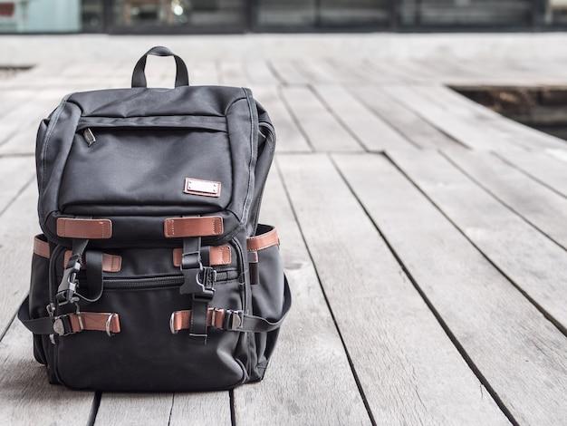 Schwarzer rucksack auf dem hölzernen hintergrund.