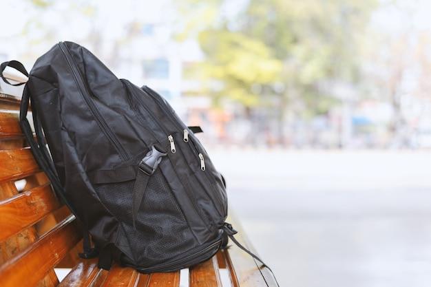 Schwarzer rucksack auf holztisch in den bushaltestellen mit weichzeichnung und über licht im hintergrund