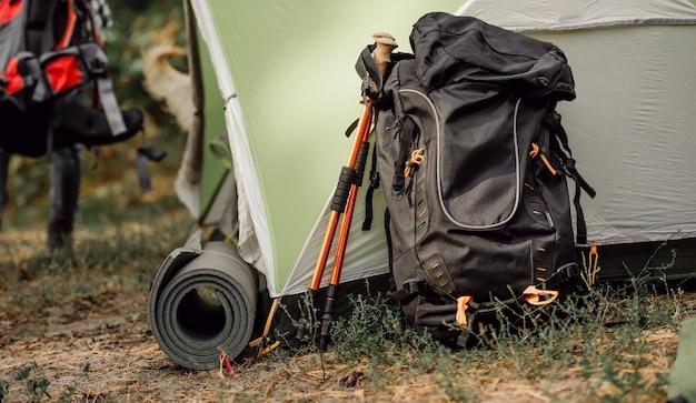 Schwarzer rucksack und karemat in der nähe des zeltes auf dem campingplatz im wald mit blick auf den touristischen...