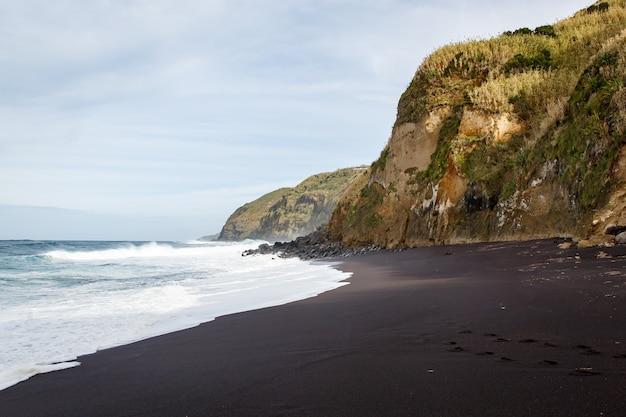Schwarzer sandstrand auf einer vulkaninsel