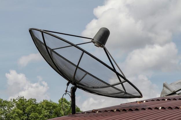 Schwarzer satelitte auf rotem dach in thailand