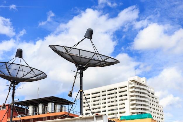 Schwarzer satellit installieren auf dem hausdach mit hintergrund des blauen himmels