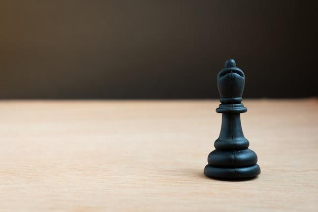 Schwarzer schachbischof mit schwarzem hintergrund