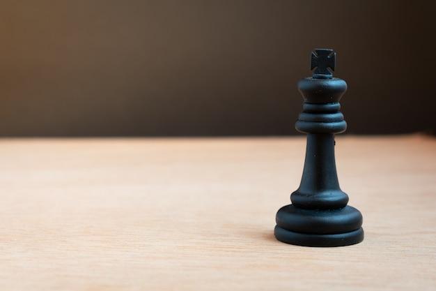 Schwarzer schachkönig mit schwarzem hintergrund