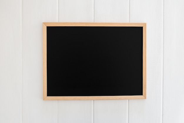 Schwarzer schiefer auf weißem hölzernem hintergrund