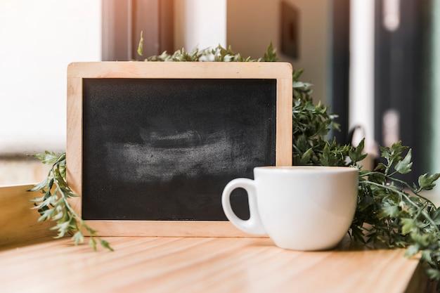 Schwarzer schiefer mit tasse kaffee auf hölzernem schreibtisch