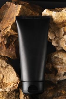 Schwarzer schlauch ohne markenzeichen mit feuchtigkeitsspendender gesichtscreme. flakon auf steinhintergrund.