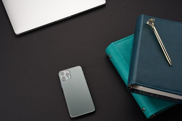 Schwarzer schreibtisch mit grünen handgefertigten notebooks, grauem laptop und smartphone