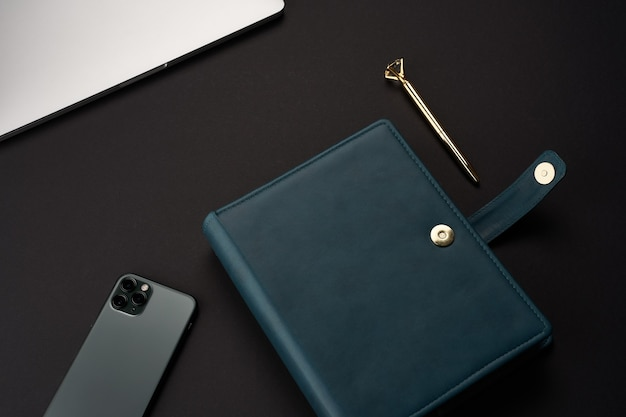 Schwarzer schreibtisch mit grünen handgefertigten notizbüchern, grauem laptop und smartphone und goldenem stift