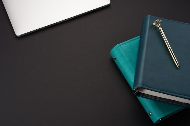 Schwarzer schreibtisch mit grünen handgemachten notizbüchern, grauer laptop