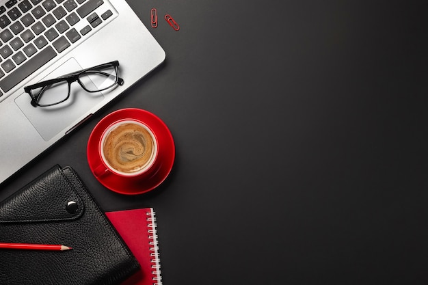 Schwarzer schreibtisch mit leerem bildschirm, laptop, notebook, tasse kaffee und anderem büro. draufsicht mit kopienraum