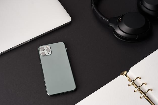 Schwarzer schreibtisch mit offenem grünem handgefertigtem notebook, grauem laptop, smartphone und headset