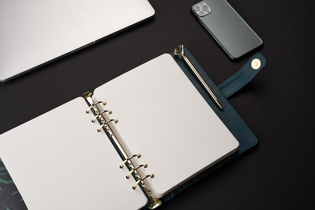 Schwarzer schreibtisch mit offenem grünem handgemachtem notizbuch mit goldenem stift und grauem laptop und smartphone