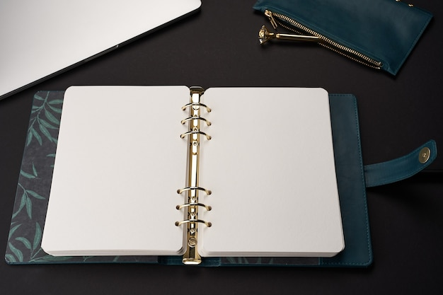Schwarzer schreibtisch mit offenem grünem handgemachtem notizbuch mit goldenem stift und grauem laptop