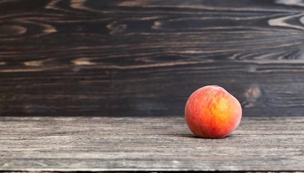 Schwarzer schwarzer tisch und wand mit einem reifen pfirsich, nahaufnahme