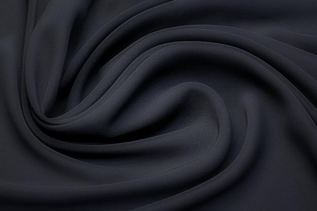 Schwarzer seidenstoff in kunstvollem layout. textur, hintergrund, muster.